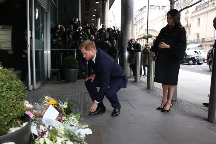 Harry leaving flowers outside the house as Meghan looks on.