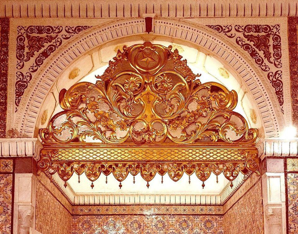 Gros plan sur une cloison dorée, ajourée d'enroulements de rinceaux, fermant l'arc en plein...