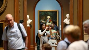 People look at paintings in the National Portrait Gallery, London August 4, 2015. London's Science Museum, and Natural History Museum are first and second most Googled Museums in the world according to London and Partners.  The same research claims London is also the most Googled city in the world for art galleries, performing arts and innovative art and design.  REUTERS/Paul Hackett