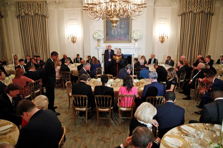 President Donald Trump bows his head in prayer as pastor Paula White leads the room in prayer during a dinner for evangelical
