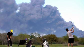 Golfers practice at the Battleground Golf Course driving range as a chemical fire at Intercontinental Terminals Company continues to send dark smoke over Deer Park, Texas, Tuesday, March 19, 2019. (Melissa Phillip/Houston Chronicle via AP)