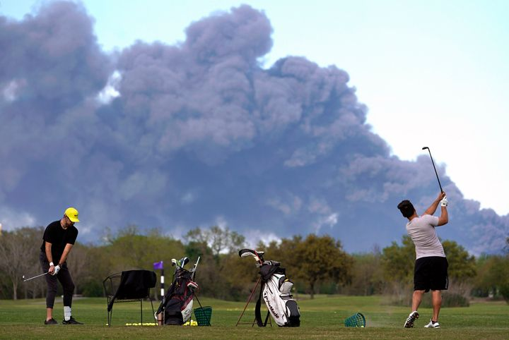 Golfers practice at the Battleground Golf Course driving range as a chemical fire at Intercontinental Terminals Company conti