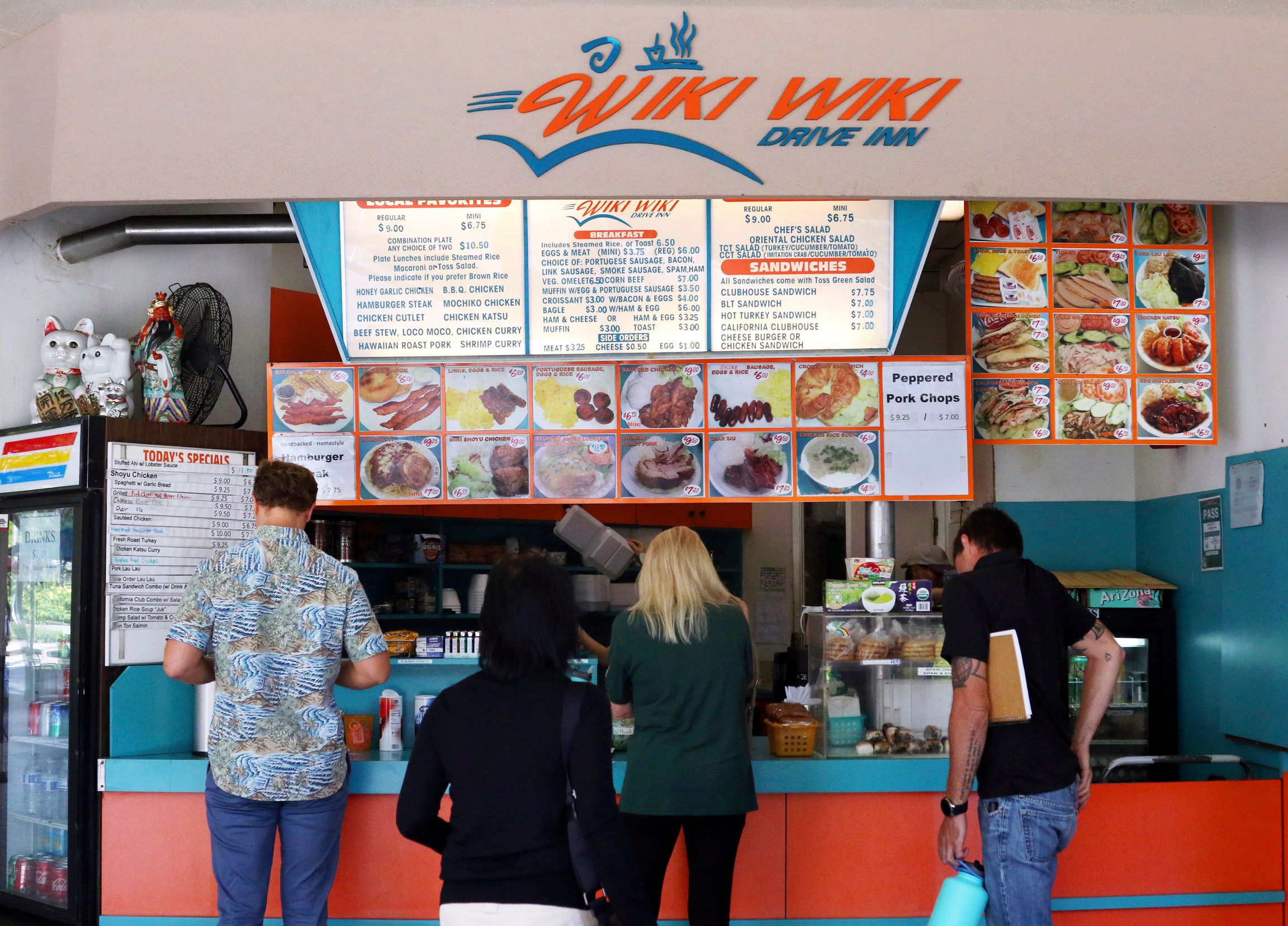 In this Thursday, March 14, 2019 photo, customers line up at the Wiki Wiki Drive Inn takeout restaurant counter in Honolulu. Hawaii would be the first state in the nation to ban most plastics used at restaurants, including polystyrene foam containers, if legislation lawmakers are considering is enacted. (AP Photo/Audrey McAvoy)