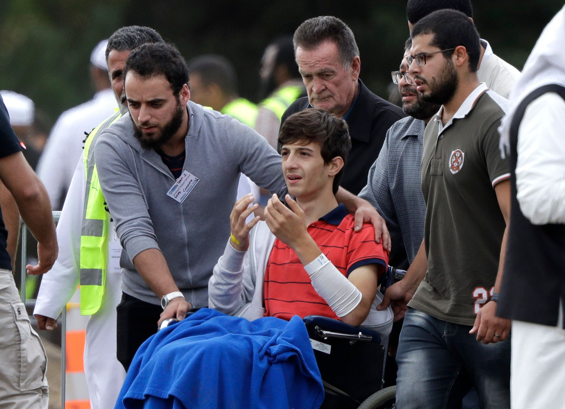 Zaed Mustafa, in wheelchair, brother of Hamza and son of Khalid Mustafa killed in the Friday, March 15 mosque shootings reacts during their burial at the Memorial Park Cemetery in Christchurch, New Zealand, Wednesday, March 20, 2019. (AP Photo/Mark Baker)