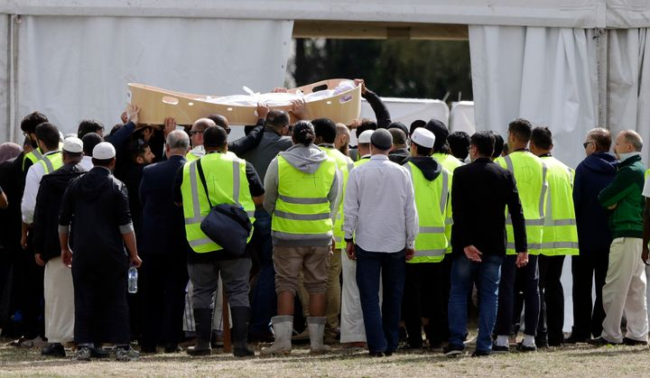 Mourners carry the body of a victim from last week's mosque shooting for a burial at the Memorial Park Cemetery in Chri