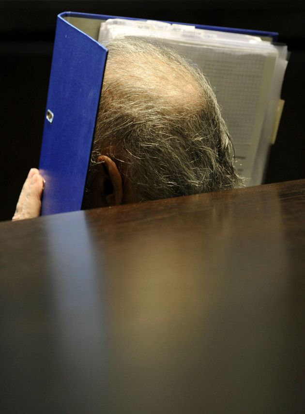 Frizl covering his face during his trial in