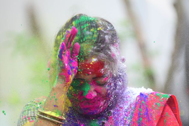 A woman smeared in colours during Holi celebrations in