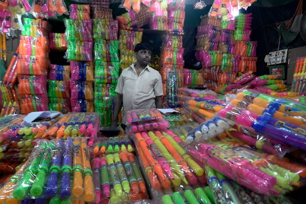 A shopkeeper sells colours and water guns in a shop in