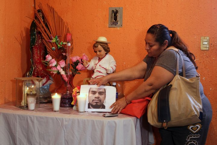 Sandra Perez places a photo of her late brother, Rene Pablo Perez, at an altar in her home in Ciudad Juarez, Mexico, on Tuesd