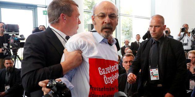 Le journaliste turc Adil Yigit évacué de la conférence de presse Merkel-Erdogan, ce vendredi 28 septembre...