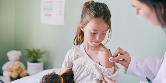 Shot of a pediatrician cleaning her young patients arm with a cotton ball