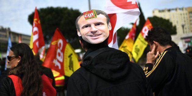 Un manifestant portant un masque à l'effigie du président Emmanuel