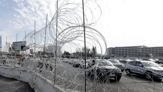 Cars line up to cross into the United States from Tijuana, Mexico, seen through barriers topped with concertina wire at the San Ysidro port of entry Monday, Nov. 19, 2018, in San Diego. The United States closed off northbound traffic for several hours at the busiest border crossing with Mexico to install new security barriers on Monday, a day after hundreds of Tijuana residents protested against the presence of thousands of Central American migrants. (AP Photo/Gregory Bull)