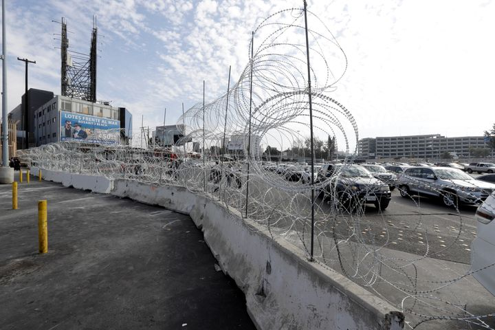 Cars lined up to cross into the United States from Tijuana, Mexico, are seen through barriers topped with concertina wire at