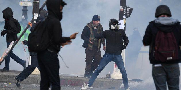 Un manifestant jette un projectile vers la police lors de la manifestation du 1er mai à
