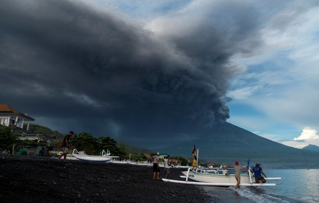Indonesia's Mount Agung volcano erupts as fishermen pull a boat onto the beach in Amed, Bali, Indonesia,...