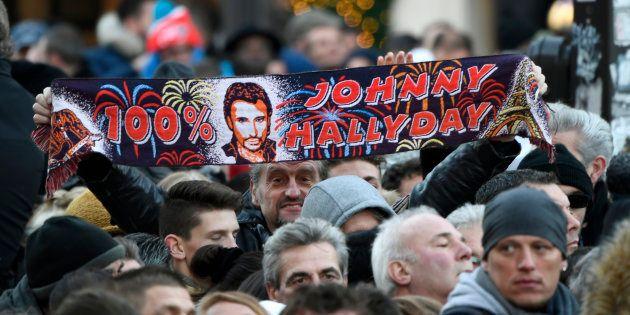 Un fan de Johnny Hallyday tendant une écharpe du chanteur à la Madeleine le 9 décembre
