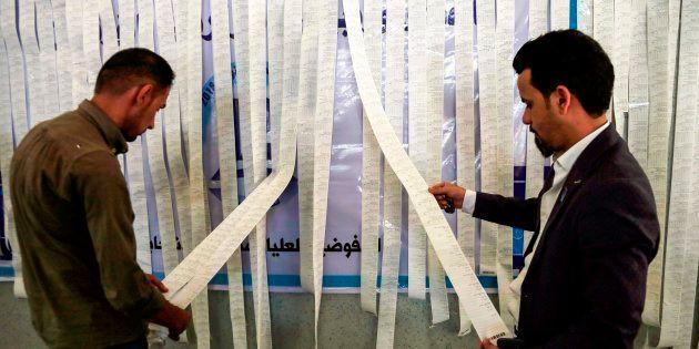 Des employés de la commission électorale irakienne examinent les imprimés électroniques des compteurs...