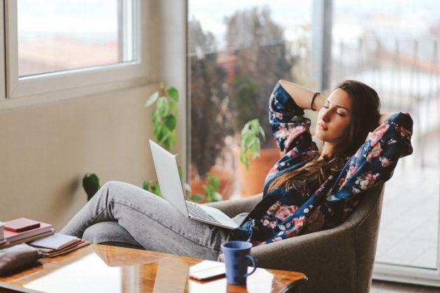 Une femme se détend, son ordinateur sur les genoux.