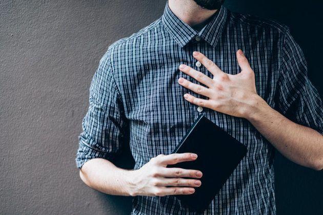 Plan serré sur un homme tenant une bible, la main sur sa poitrine.