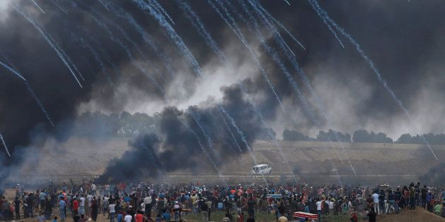 Des gaz lacrymogènes sont tirés par l'armée israélienne sur les Palestiniens manifestant pour le retour...