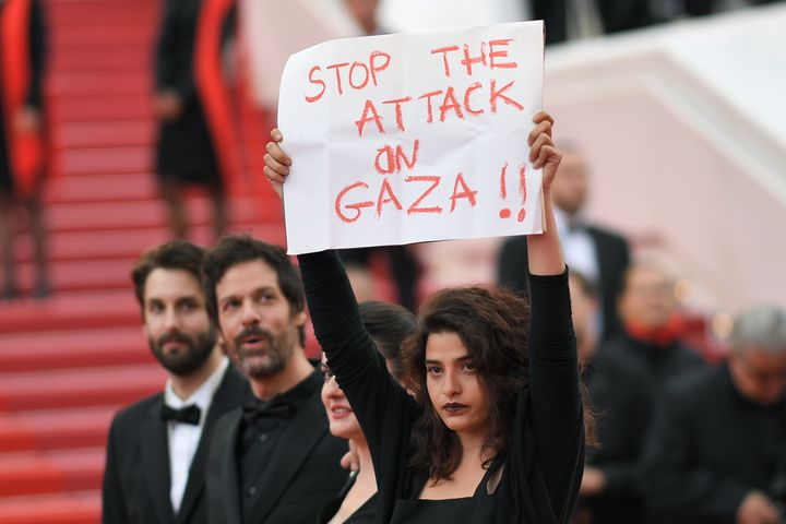 """French-Lebanese actress Manal Issa (R) holds a sign reading """"Stop the Attack on Gaza"""" as she arrives on May 15, 2018 with Syrian director Gaya Jiji (2ndR) and Greek-South African film director Etienne Kallos (2ndL) for the screening of the film """"Solo : A Star Wars Story"""" at the 71st edition of the Cannes Film Festival in Cannes, southern France.  / AFP PHOTO / LOIC VENANCE"""