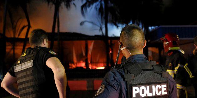 Les forces de l'ordre intervenant près d'une maison incendiée à la suite des résultats du