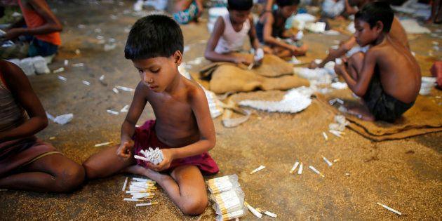 Des enfants remplissent des cigarettes vides manuellement avec du tabac cultivé localement, dans une...