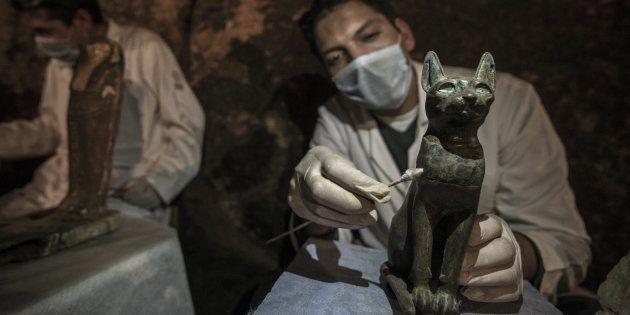 Un archéologue nettoie une statue de chat en bronze datant de l'Égypte ancienne, le 10 novembre à
