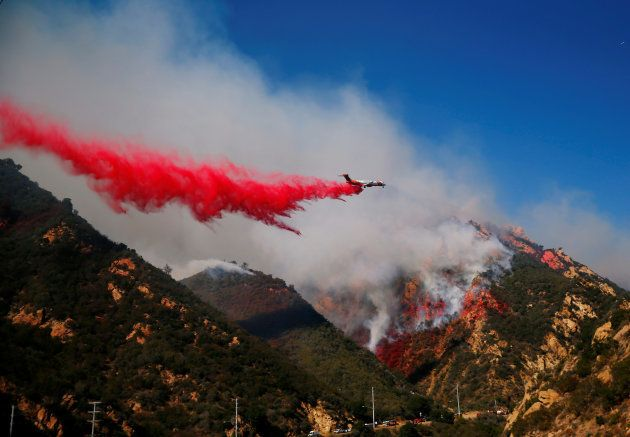 An aircraft drops flame retardant as firefighters battle the Woolsey Fire as it continues to burn in...
