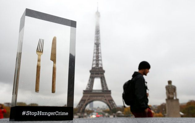 A man walks in front of the Eiffel Tower during the launching of international campaign StopHungerCrime...