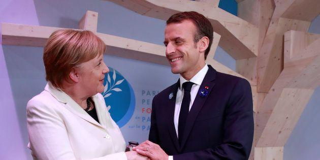 Angela Merkel et Emmanuel Macron échangent une poignée de main lors du Forum pour la Paix organisé à...