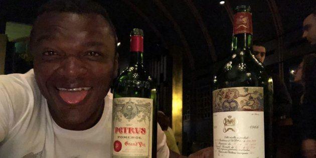 Marcel Desailly accompagné d'une bouteille de Petrus qui semble le rendre
