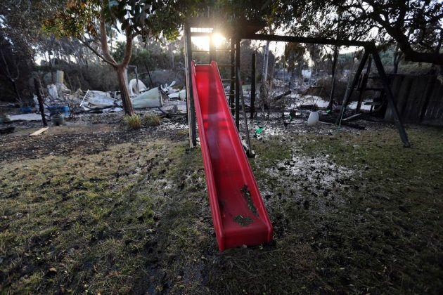 Une balançoire et un toboggan d'enfant près d'une maison détruite par l'incendie Woolsey dans la rue...