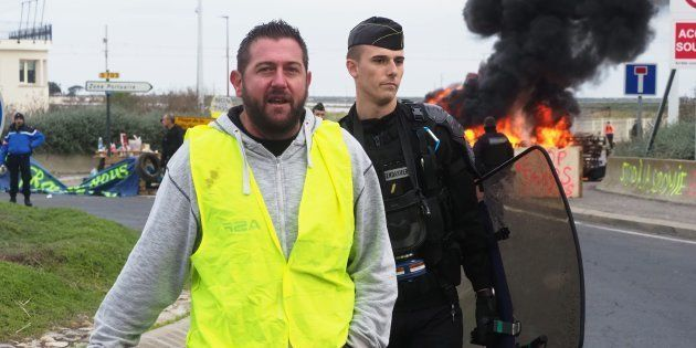 Un membre des gilets jaunes escorté par un gendarme mardi 20 novembre à