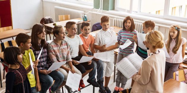 High angle view of elementary teacher practicing with group of kids during music lecture in the classroom.
