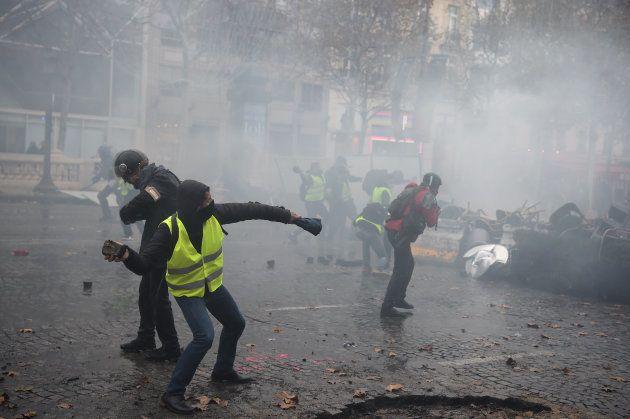 Un manifestant jette des pavés sur les Champs-Élysées, ce samedi 24