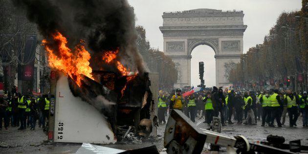 Sur les Champs-Élysées, des gilets jaunes érigent des barricades et lancent des