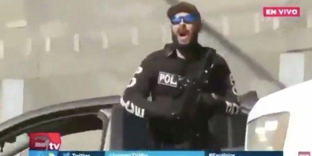 Un policier s'apprêtant à faire feu à l'aide de balles de caoutchouc contre les migrants venus réclamer...