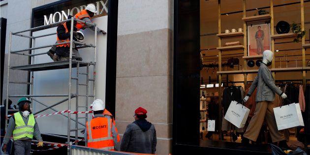 Des ouvriers protègent la devanture d'un magasin sur l'avenue des Champs-Élysées, ce vendredi 30 novembre,...