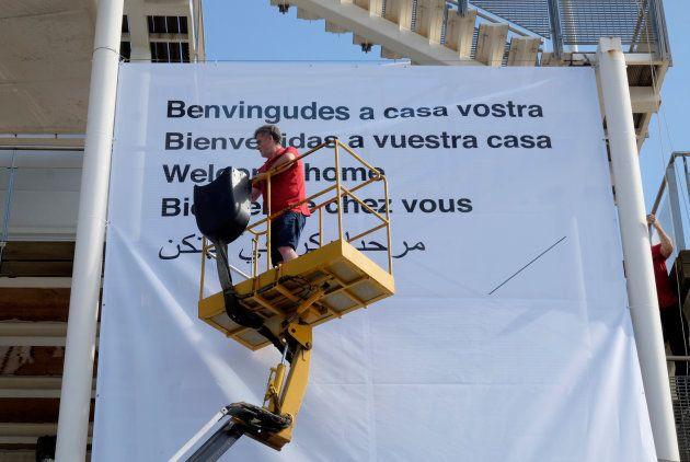 Un volontaire de la Croix Rouge installe une bannière souhaitant la bienvenue aux migrants de l'Aquarius,...