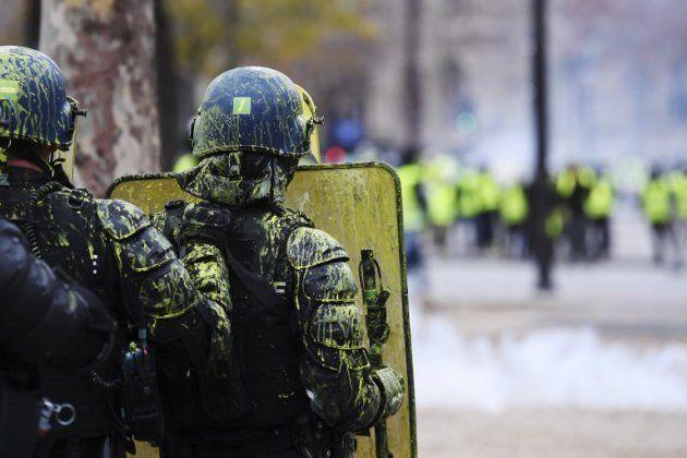 Sur les Champs-Élysées, les gilets jaunes aspergent les policiers de peinture