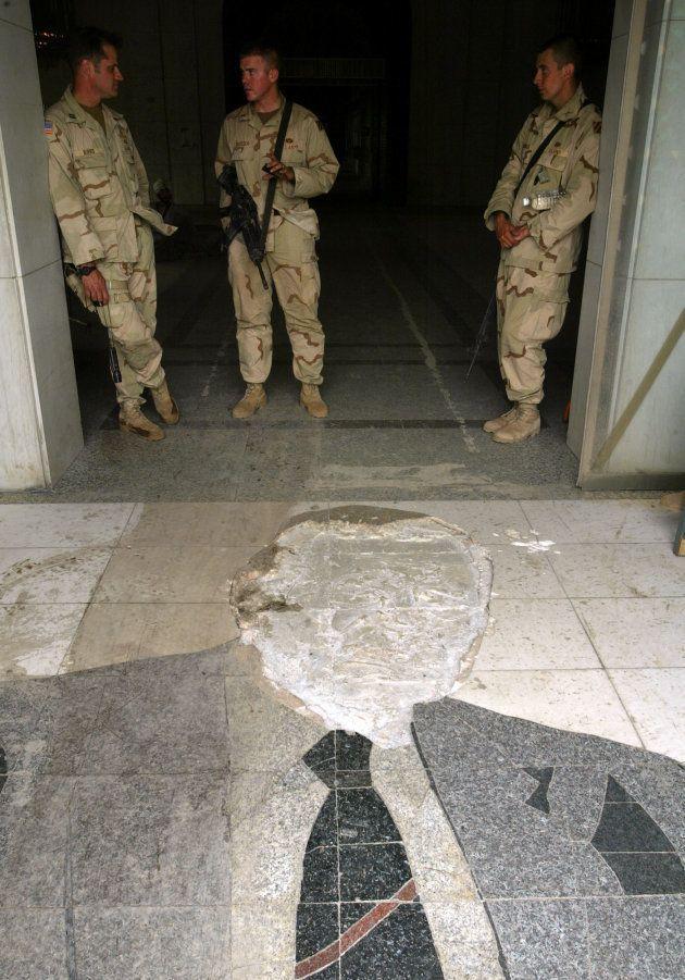 Des soldats américains devant la mosaïque de George Bush, déjà partiellement détruite en mars