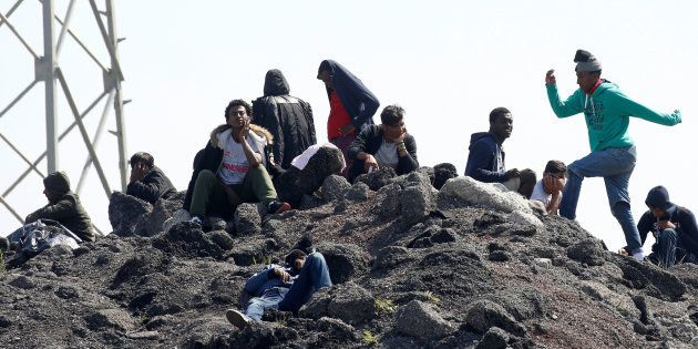 Migrants gather on a heap of loose earth near the