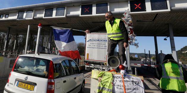 Un manifestant des gilets jaunes brandissant un drapeau tricolore à proximité d'Aix-en-Provence