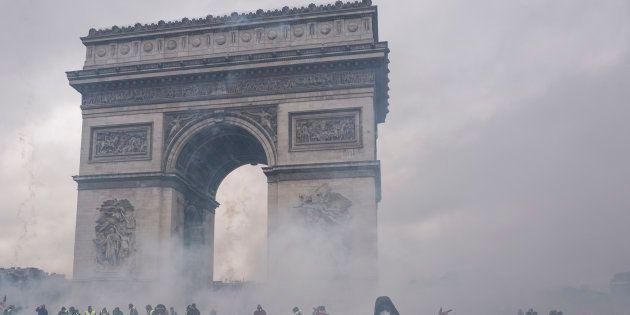 Des gilets jaunes au milieu des gaz lacrymogènes devant l'Arc de Triomphe, samedi 1er