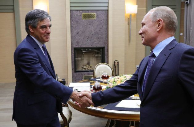 Russia's President Vladimir Putin (R) shakes hands with French former Prime Minister Francois Fillon...