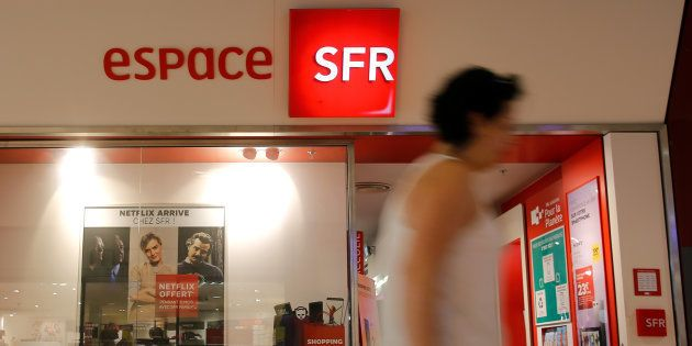 A woman walks past a shop of French telecoms operator SFR in Saint-Sebatien-sur-Loire near Nantes, France,...