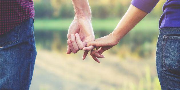 Un homme et une femme en couple se tiennent la main.