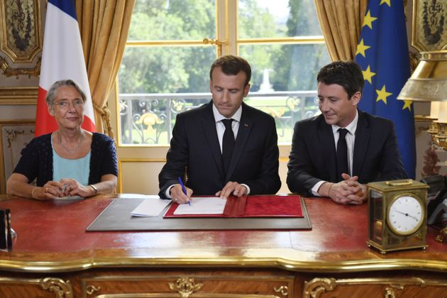 French President Emmanuel Macron (C), flanked by French Transports Minister Elisabeth Borne (L) and French...